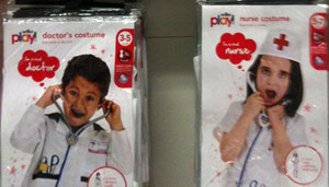 Toy packaging showing boy wearing Doctor outfit, girl wearing nurse outfit